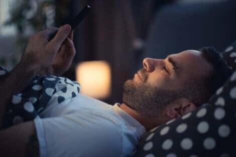 bir adam yatakta telefonuyla oynuyor