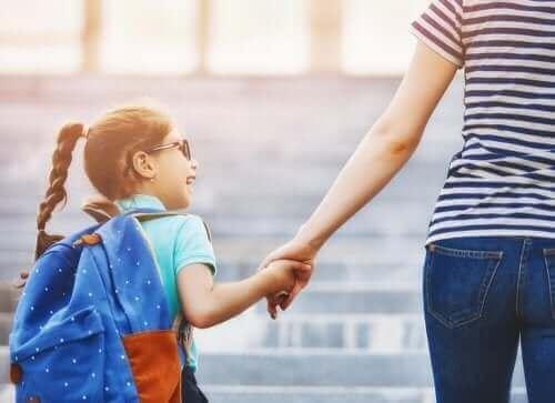 Bir yetişkinin elini tutmuş bir şekilde yürüyen bir çocuk.