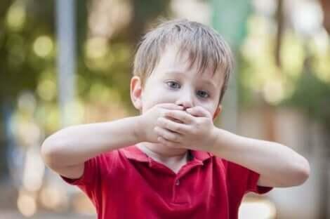Küçük bir çocuk ağzını elleriyle kapatıyor.
