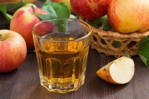 Bir bardak elma suyu ve yanındaki elmalar.