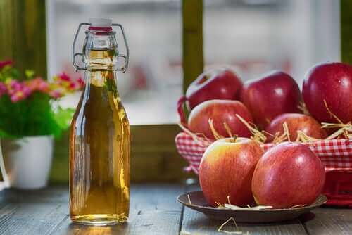 Bir şişe elma sirkesinin yanında duran elmalar.
