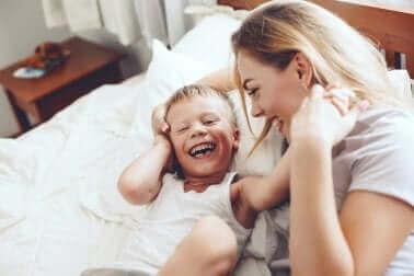 Bir anne çocuğuyla beraber yatakta kahkaha atıyor.