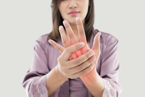 eli artrit nedeniyle ağrıyan kadın