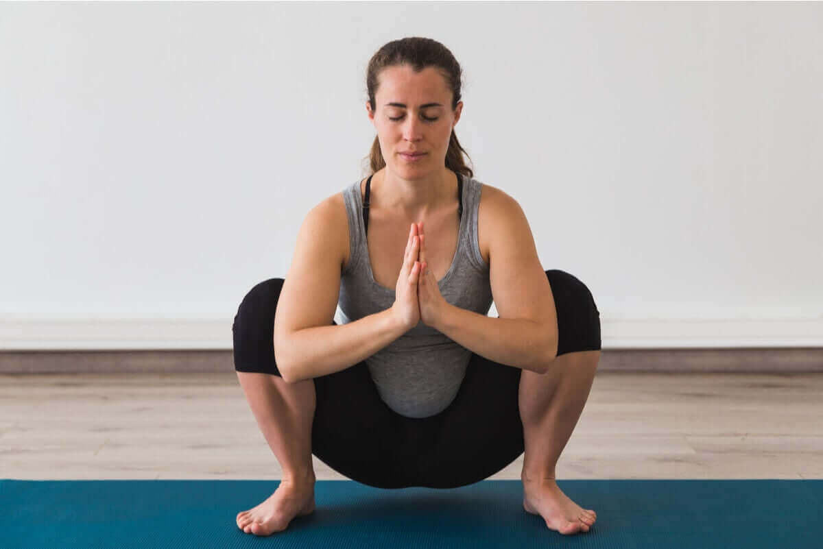 matta çömelmiş yoga yapan kadın