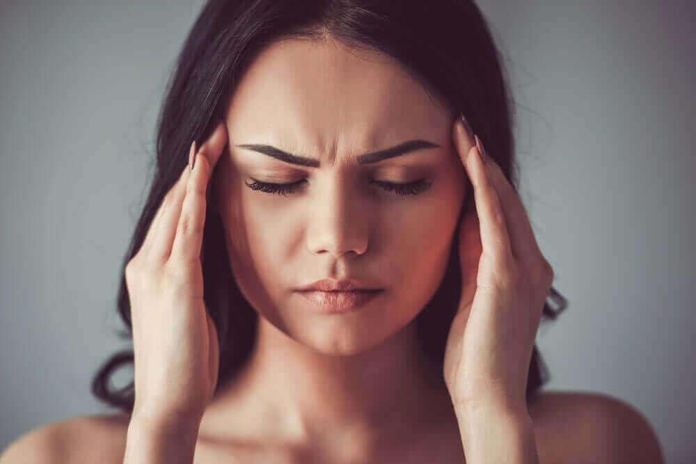 ağrıyan başını tutan kadın
