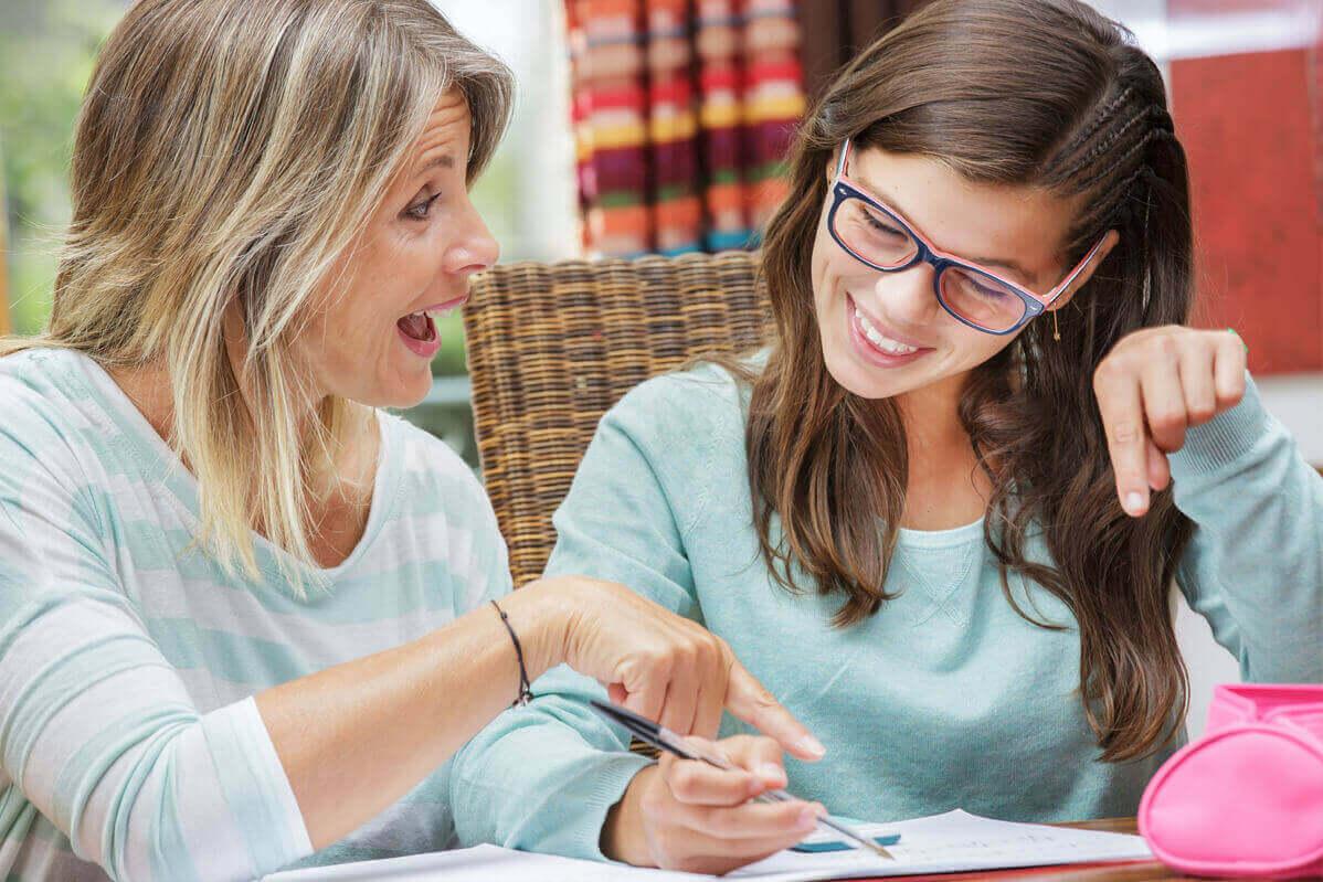 bir yazıya bakıp gülerek konuşan iki kişi