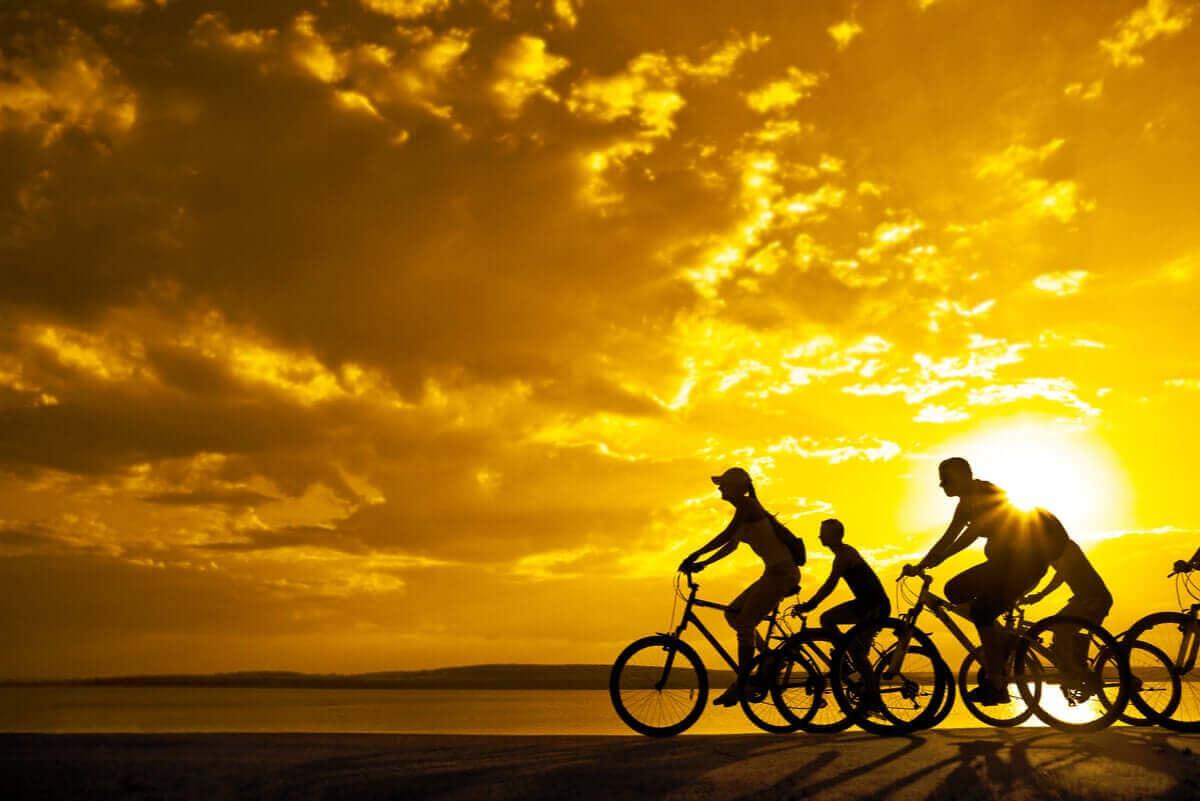 gün batımında bisiklete binen insanlar