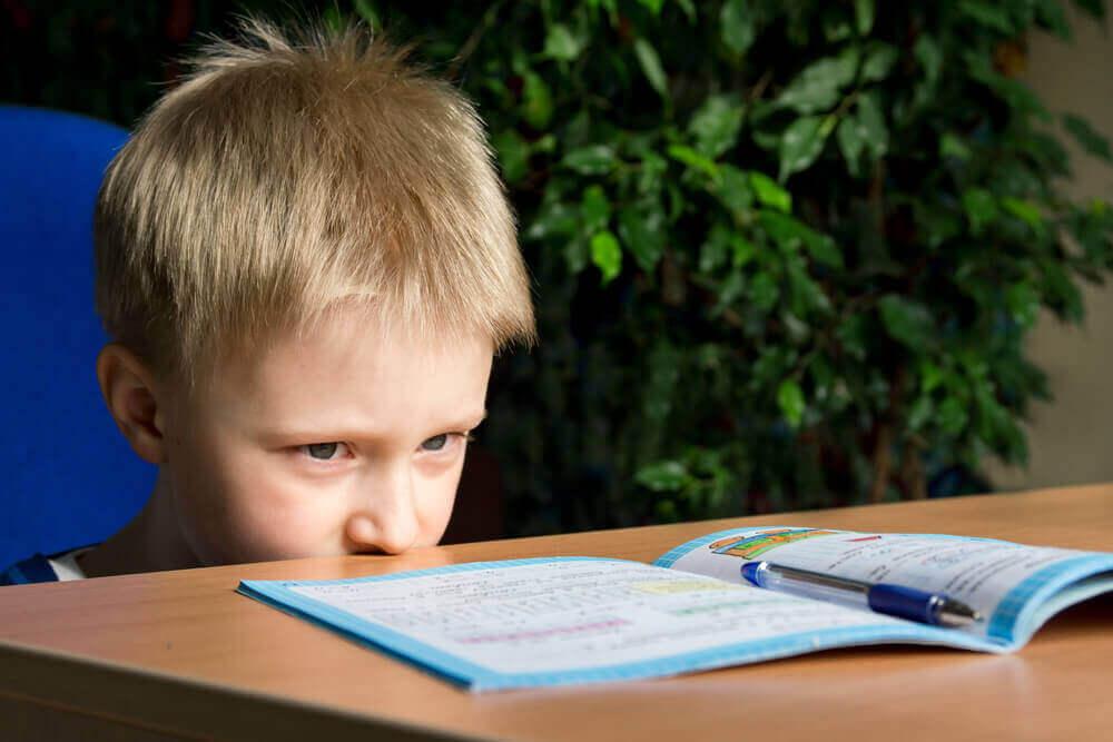 masadaki ders kitabına bakan çocuk