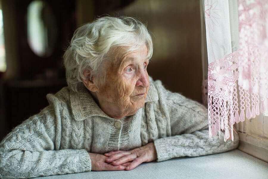camdan bakan üzgün yaşlı kadın
