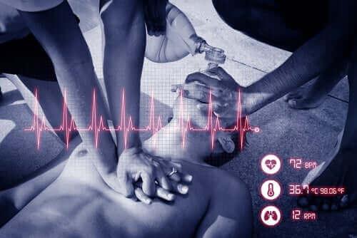 kalp masajı yapan iki kişi