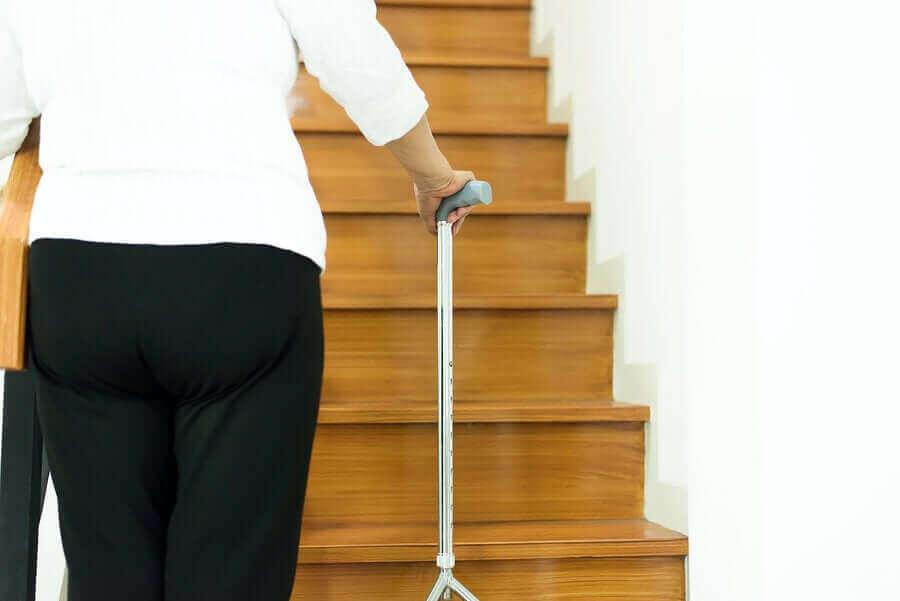 merdivene bastonla yürüyen kişi
