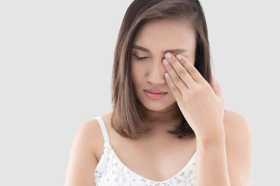 ağrıyan gözünü tutan kadın