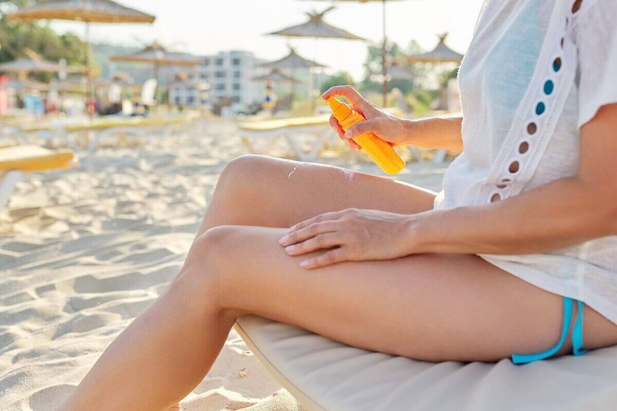 bacaklarına güneş kremi süren kadın