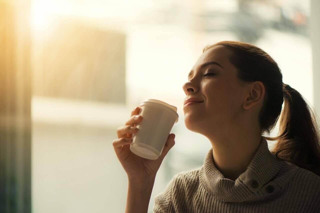 kahvesini koklayan mutlu kadın