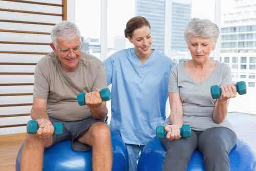 spor yapan yaşlı inmsanlar ve onlara yardım eden sağlık görevlisi